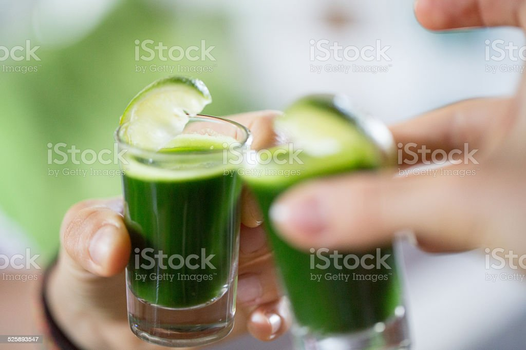 People toasting wheat grass stock photo