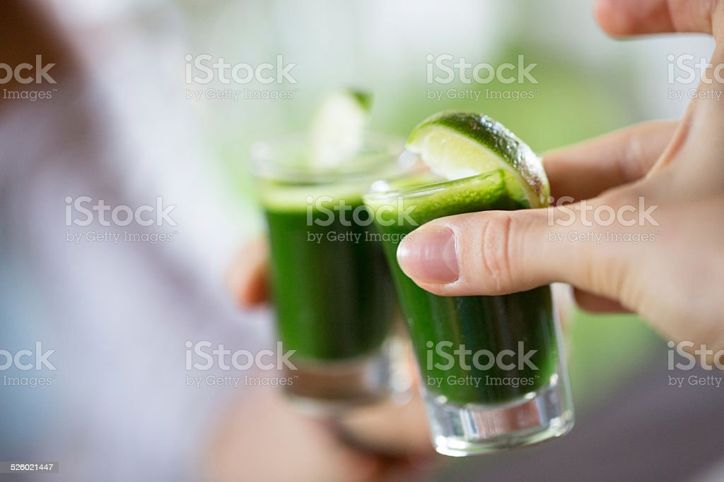 People toasting wheat grass stock photo