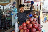Madaba, Jordan - February 16, 2020. Unidentified people trade pomegranate juice in street of Madaba, Jordan on February 16, 2020. Madaba is the capital city of Madaba Governorate in central Jordan.
