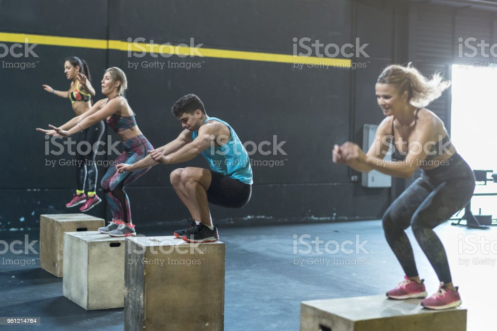 People training in gym class jumping on boxes stock photo