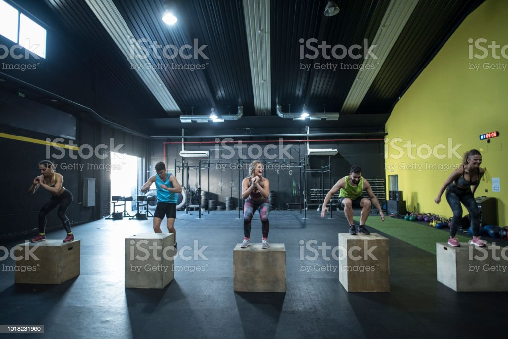 People training in gym jumpin on boxes stock photo