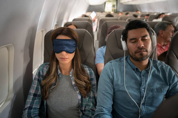 People traveling by air and sleeping on the plane People traveling by air and sleeping on the plane wearing headphones and an eye mask - travel concepts jet lag stock pictures, royalty-free photos & images