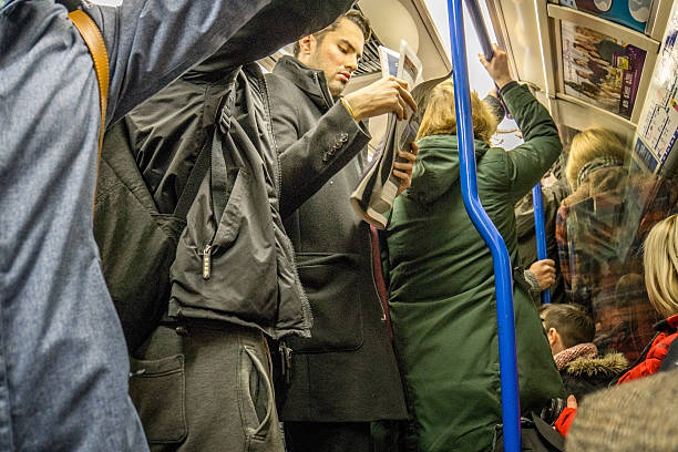 people travelling on crowded london underground train - peuples photos et images de collection