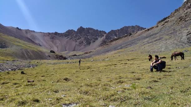 People trekking from Pshart valley through Gumbezkul pass to Madiyan in Tajikistan Pamir highway. stock photo