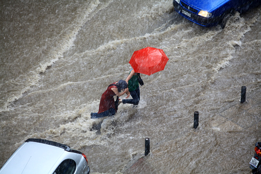 People try to cross a flooded road