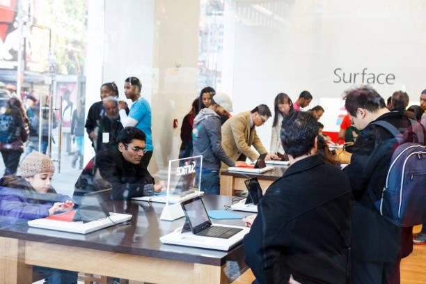 menschen versuchen microsoft surface tablet in times square, manhattan - microsoft windows stock-fotos und bilder