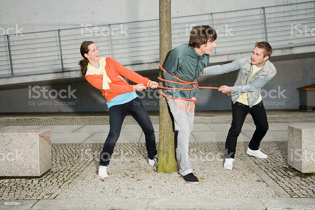 People tying man to tree royalty-free stock photo