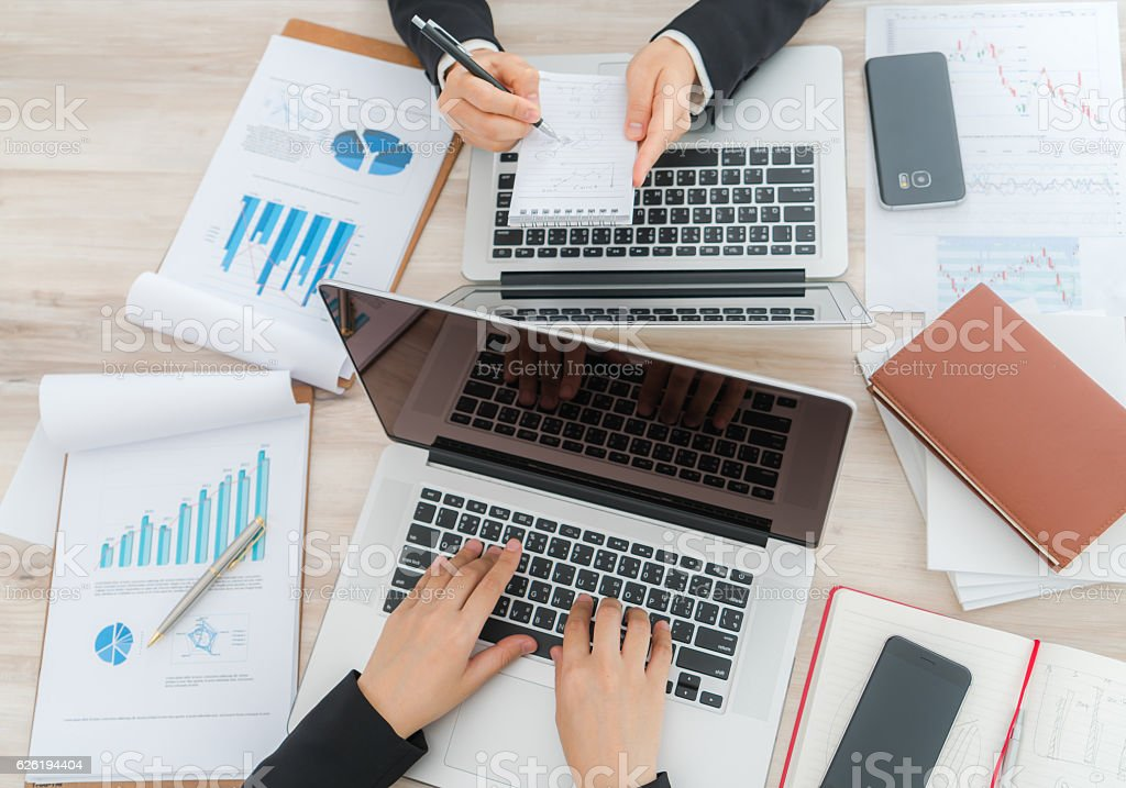 People typing on laptops surrounded by financial charts stock photo