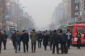 Beijing, China - December 8, 2015: People walking on the street under a heavy smog day . ŒSome people wearing mask with air filter to against air pollution.
