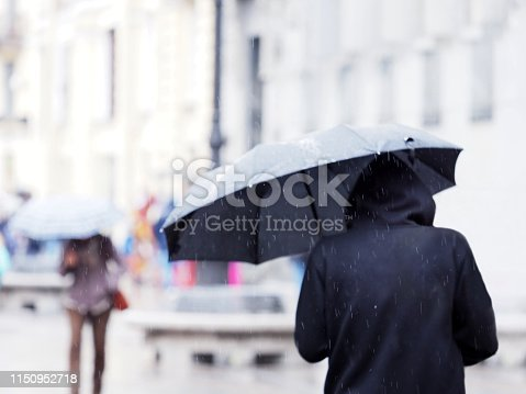 People under umbrellas on a city street in the rain