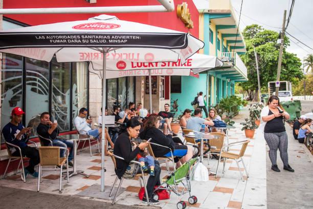 menschen nutzen kostenfreies wlan mit smartphones in einem kaffee, varadero, kuba - www kaffee oder tee stock-fotos und bilder