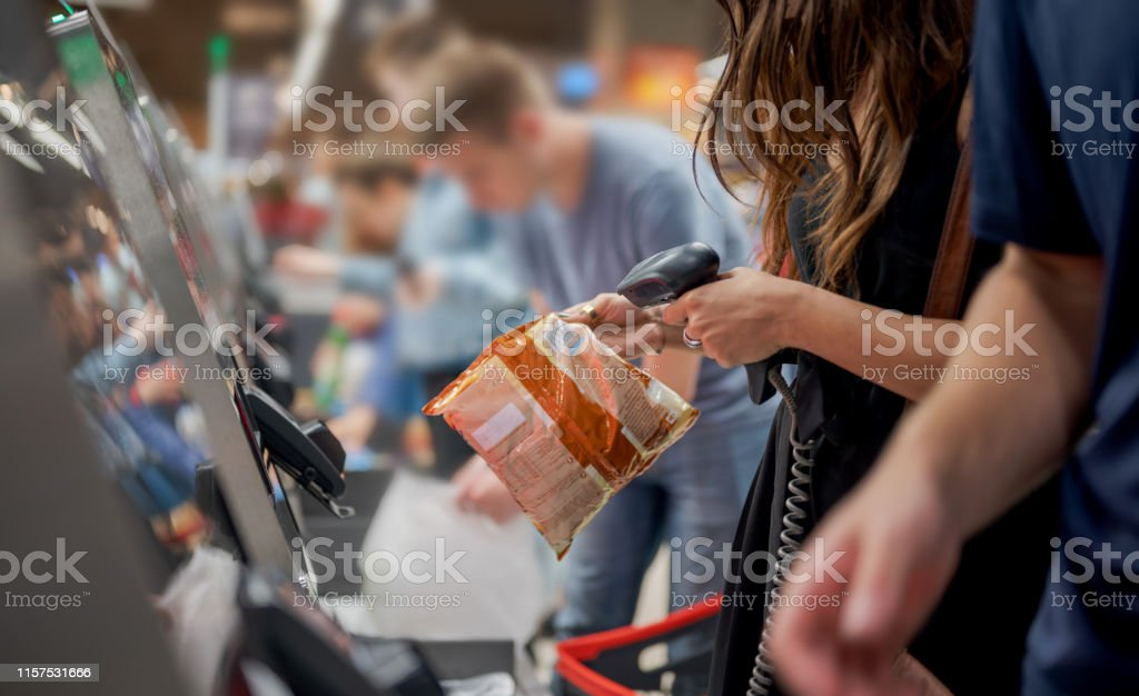 Group of people in a row using self service checkout, Nikon Z7