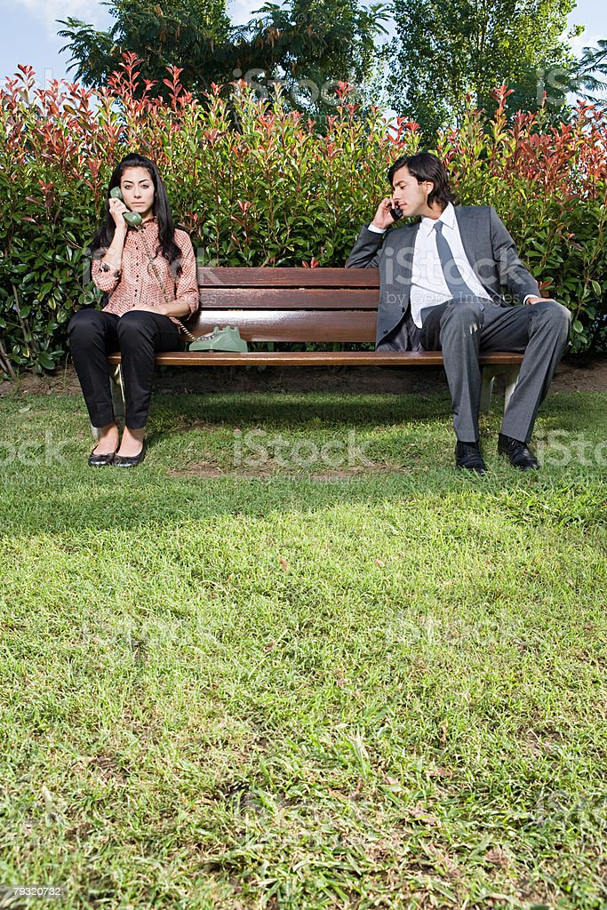 People using telephones on a park bench 免版稅 stock photo