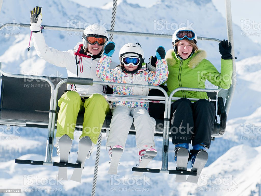 People vacationing and riding on ski lift stock photo