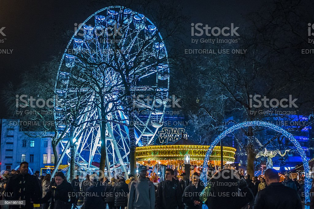 People visit an illuminated Christmas fairground in Leicester Square, London stock photo