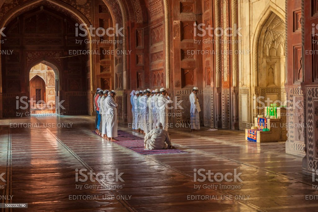 people visit Taj Mahal in India and pray in the mosque stock photo