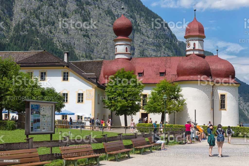 People visiting St. Bartholomew's Church at Konigssee in Germany stock photo