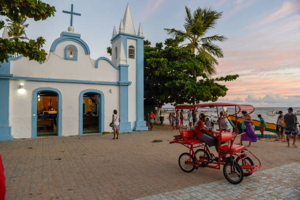 People visiting the colonial church of mainly square in the Praia do Forte on Brazil stock photo