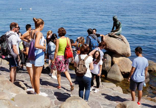 menschen besuchen die kleine meerjungfrau - kleine meerjungfrau kunst stock-fotos und bilder