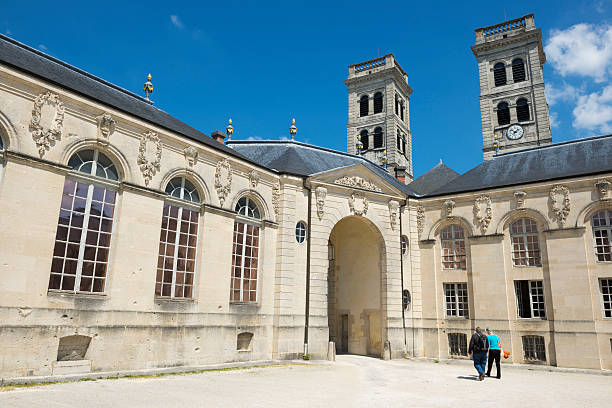People visiting Verdun, France Verdun, France - May 17, 2014: Two people walk in the courtyard of the Centre Mondial de la Paix in Verdun, France. The towers of the Verdun Cathedral are in the background. verdun stock pictures, royalty-free photos & images
