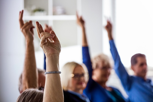 Senior people voting during group therapy, raising hands. They are discussing about mental wellbeing. Close up of hands.