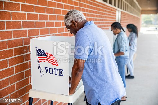 Three African American people voting in an election