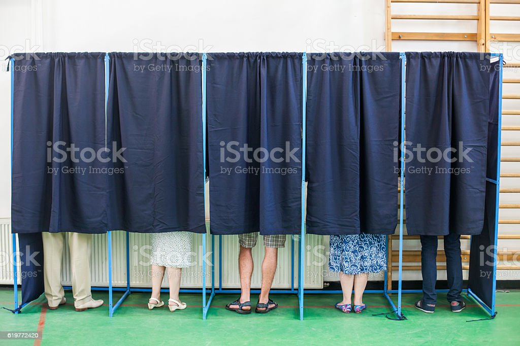 People voting in booths stock photo