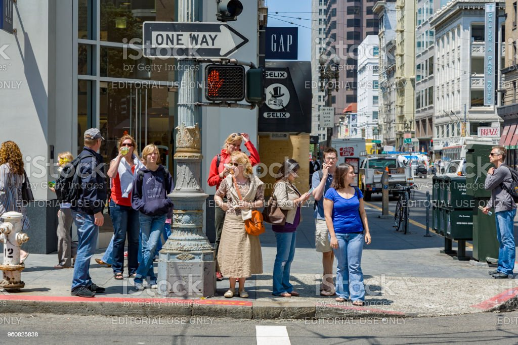 people wait at a pedestrian crossing for green light to cross the street in San Francisco stock photo