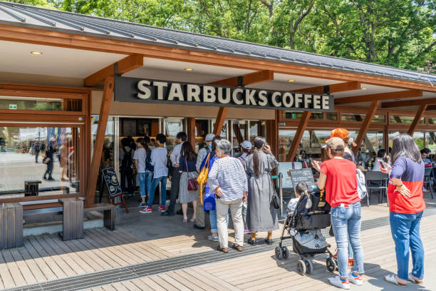 People wait in line at the Starbucks inside the famous Ueno Park in Tokyo, Japan stock photo