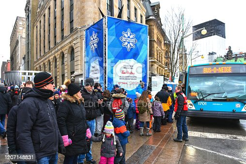 Ottawa, Canada - February 16, 2020: People wait in line on Sparks Street for the Snow Bus to take them to a different venue of the annual Winterlude Festival.
