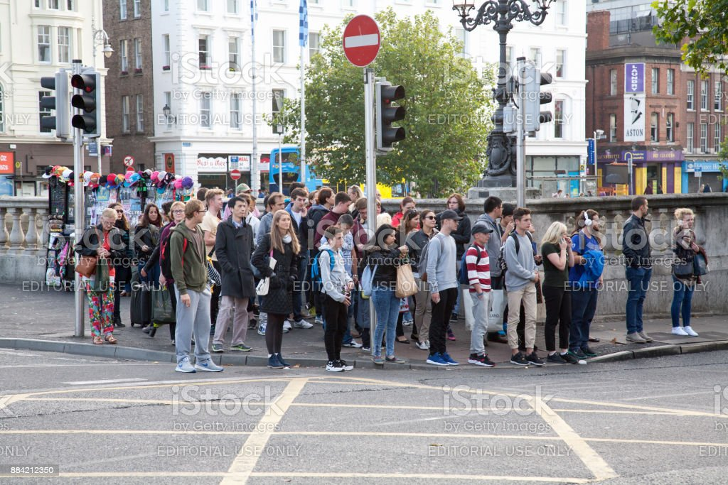 People waiting at traffic lights near O'Connell bridge. stock photo
