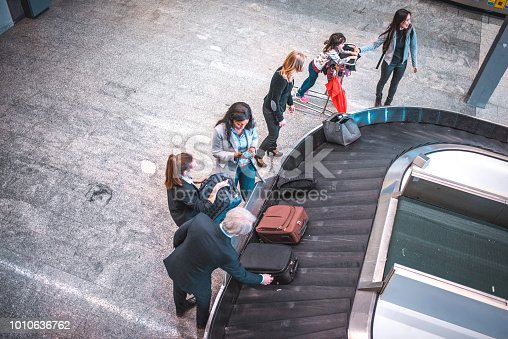 High angle view of passengers waiting for luggage at airport. People are standing by conveyor belt. They are looking for their baggage.