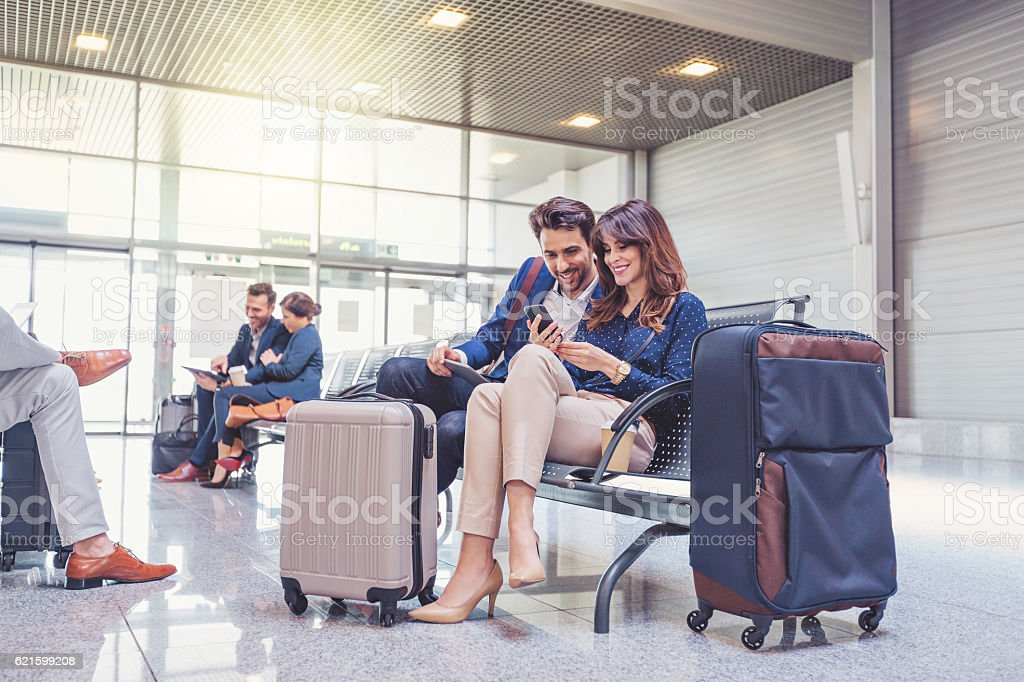 People waiting for flight at airport lounge stock photo