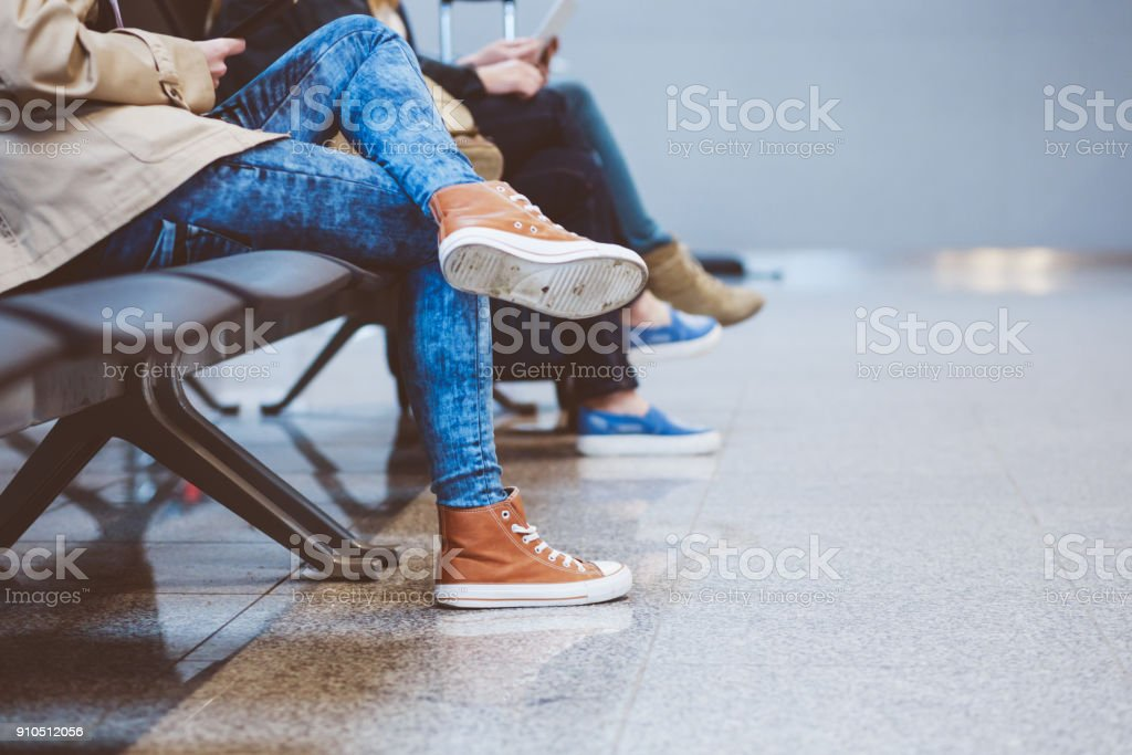 People waiting for flight in airport lounge, close up of legs stock photo