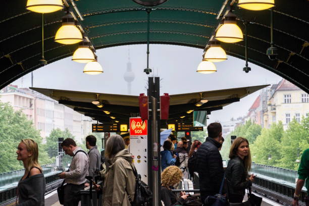 menschen warten auf zug der u- und s-bahn s-bahn station schonhauser allee mit fernsehturm television tower im nebligen hintergrund in berlin, deutschland - u bahn stock-fotos und bilder