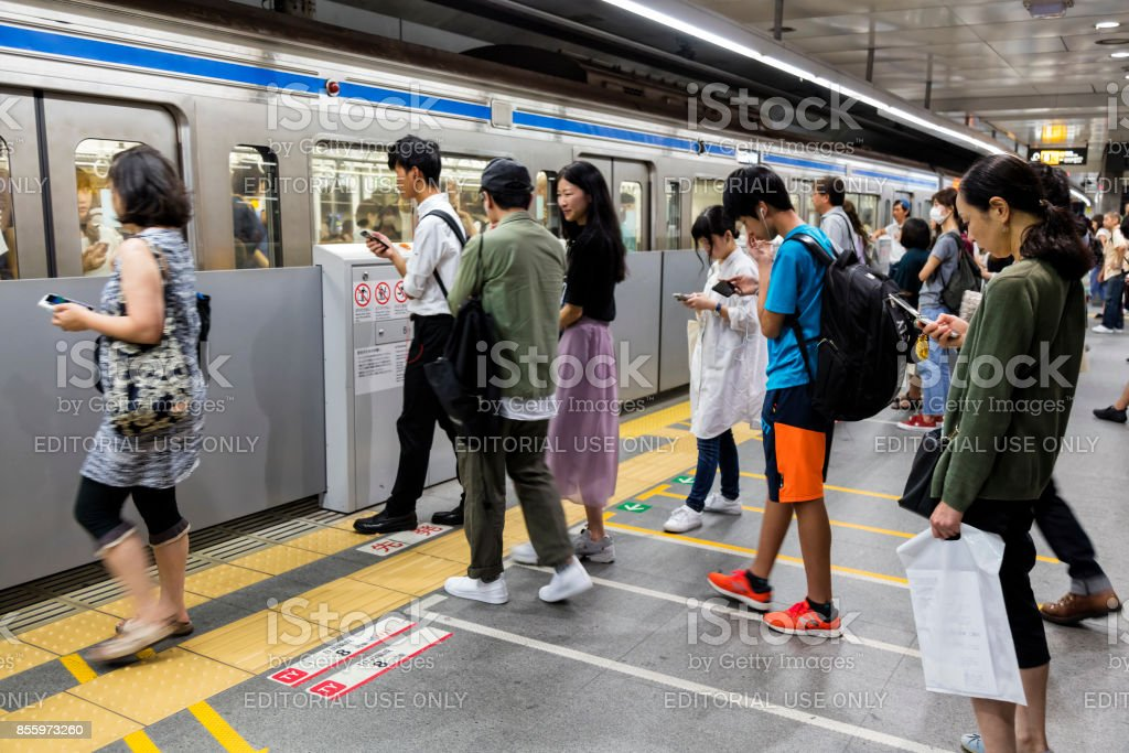 Commuters waiting for train on subway station platform, Tokyo Metro,...