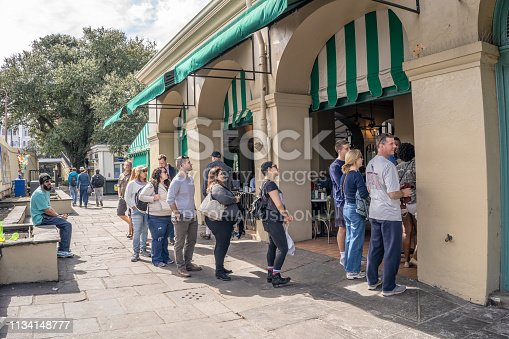 New Orleans, Louisiana / USA - February 14, 2019: People wait in line at the to-go counter at the famous Cafe Du Monde restaurant, for beignets, in the French Quarter.
