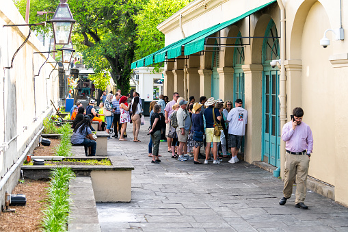New Orleans, USA - April 23, 2018: People in line queue waiting to order food at Cafe Du Monde restaurant sign famous for beignet donuts and chicory coffee