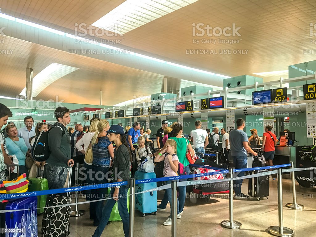 People waiting in line for flight check-in, Barcelona Airport - foto de acervo