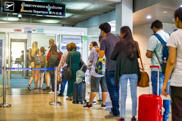 People waiting in line for security check at airport domestic departures stock photo