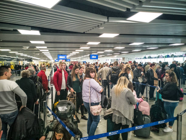 People waiting in line for security check at airport European International departures stock photo