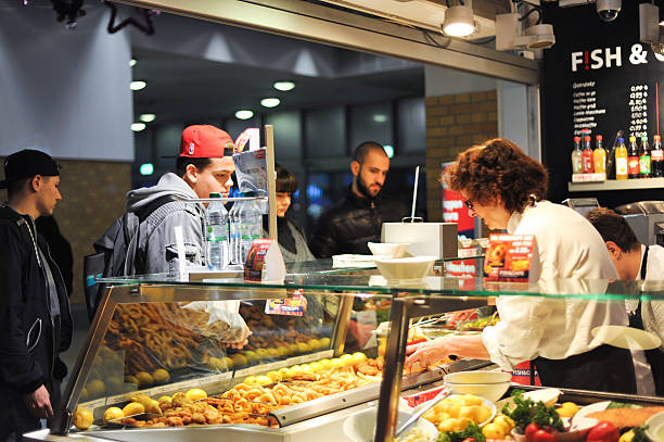 People waiting in line for snack in fish and chips stores stock photo
