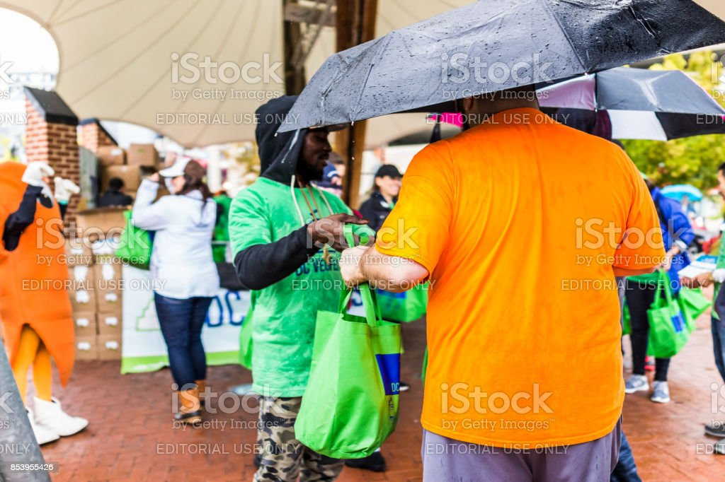 People waiting in line queue holding umbrellas during heavy rain at vegetarian vegan VegFest with man handing out free tote food goodie bags stock photo