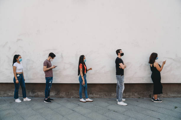 People waiting in line to enter in a store - Social distancing concept stock photo