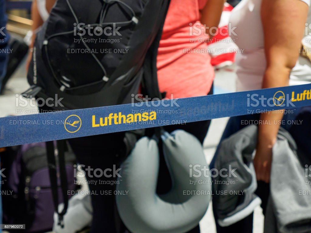 People waiting in line with Lufthansa logo on queue barrier stock photo