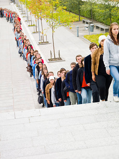people waiting in long line - long stock pictures, royalty-free photos & images