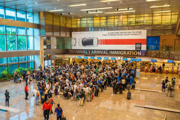 people waiting in queue at arrival immigration of changi airport - emigration and immigration stock photos and pictures