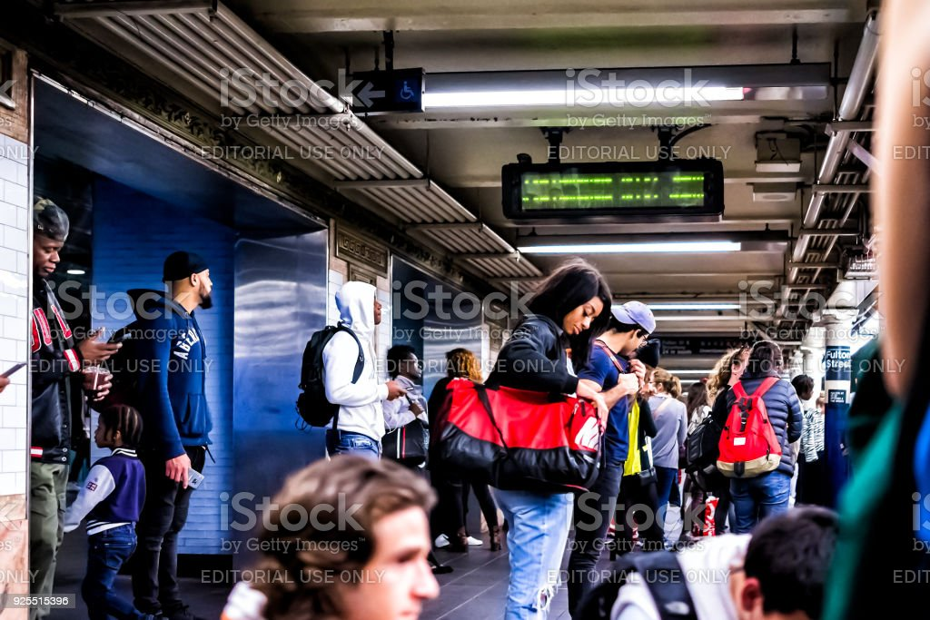 People waiting in underground transit empty large platform in NYC Subway Station in downtown, looking at phones on Fulton street stock photo