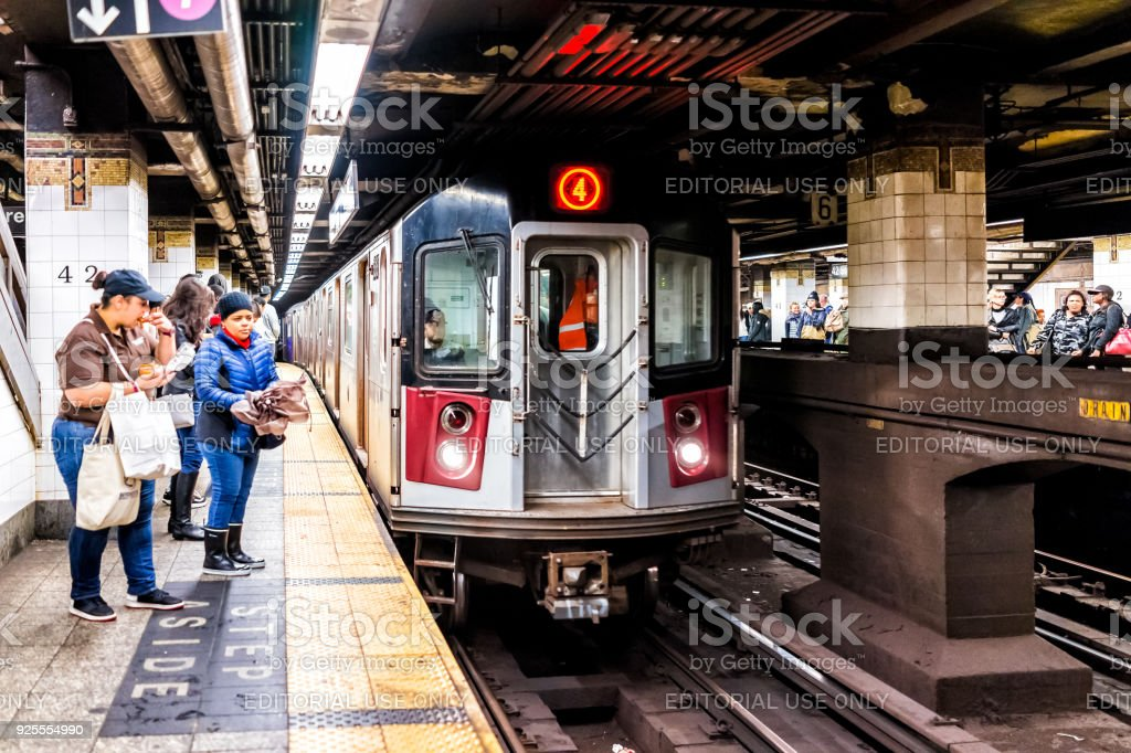 People waiting in underground transit empty large platform in NYC Subway Station, railroad tracks, woman eating, incoming train stock photo
