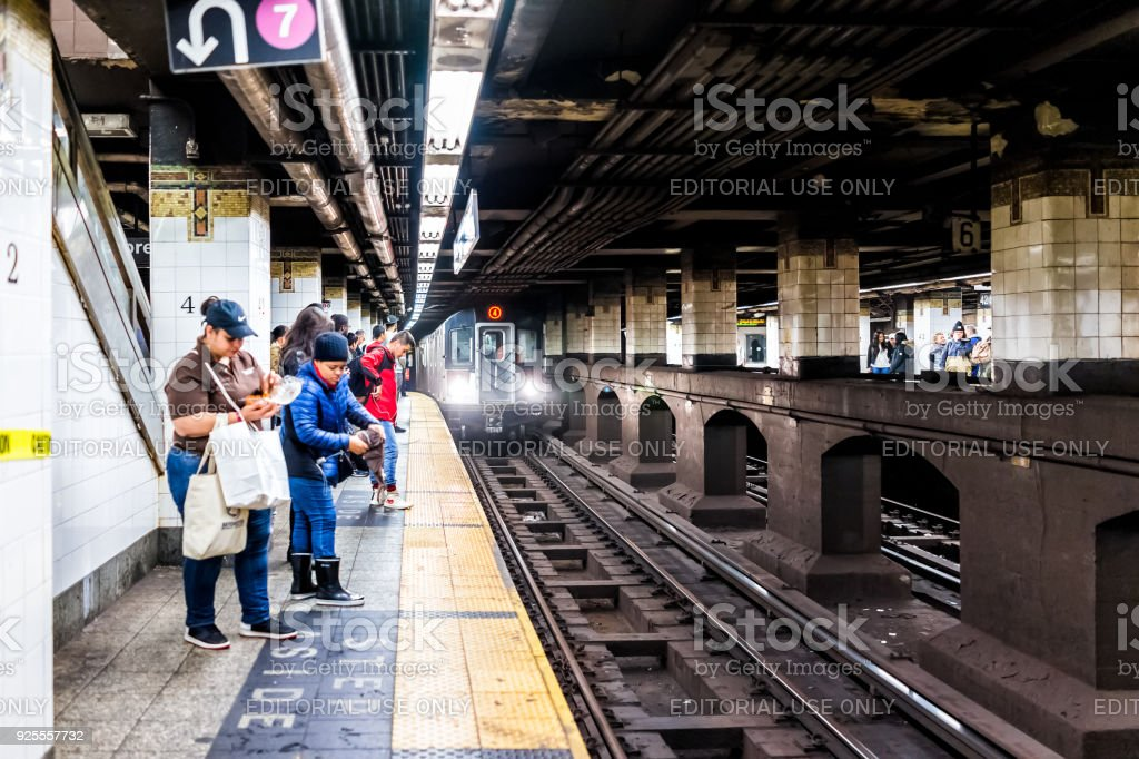 People waiting in underground transit empty large platform in NYC...
